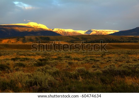 Soft, warm light filtered through storm clouds over Tetons gives golden glow to Jackson Hole in Grand Teton National Park, Wyoming.  Snow blankets Gros Ventre Mountain Range east of Jackson Hole.