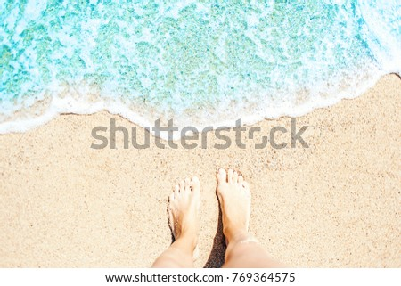 Soft wave of blue ocean on sandy beach Background with women feets, view from above. Tropical summer vacation concept.