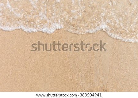 Soft wave of the sea on the sandy beach with white clean foam. Copy space
