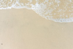 Soft wave with blue ocean on sandy beach. Empty space can be used as background for display or montage your top view products.