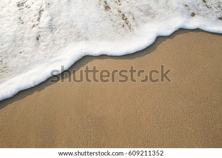 Soft wave with bubbles on sandy beach #609211352