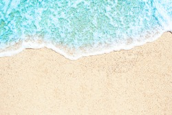 Soft waves with foam blue ocean sea on  golden sand with copyspace. Summer beach vacations background