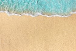 Soft waves with foam of ocean on the sandy beach background