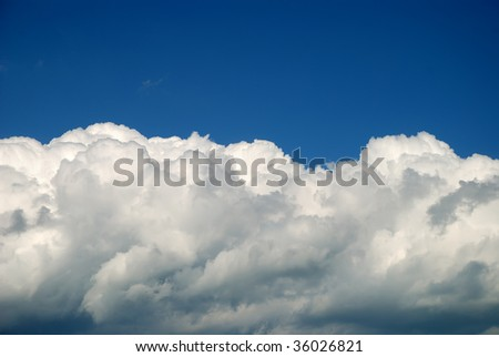 Soft white clouds against dark blue sky