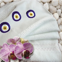 Soft white towel with embroidery Turkish blue bead on marble background. Hammam, Spa, bath set with flower and evil eye lucky glass eye drawing.