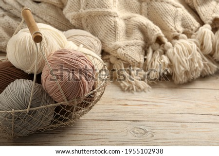 Soft woolen yarns and knitted fabric on white wooden table, closeup. Space for text Stock photo ©