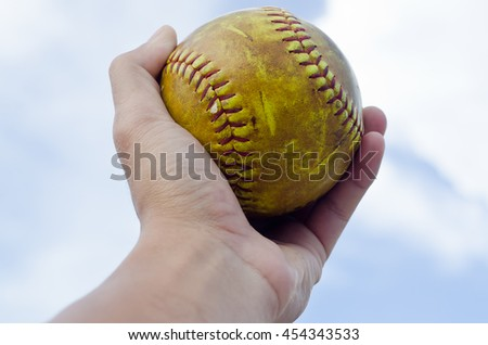softball in hand ,sky background
