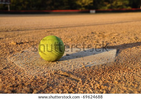 Softball on home plate on ball field