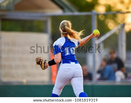 Softball pitcher throwing to first base and player sliding into base safely