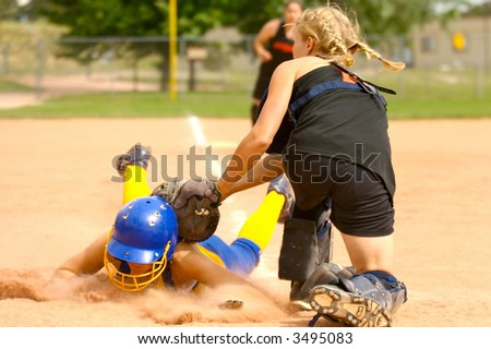 Softball player being tagged sliding head-first into home-plate