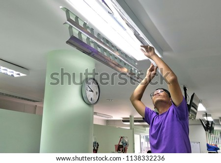 Softly focus of Asian man in purple T-shirt is repairing damaged fluorescent lamp on ceiling in hospital room