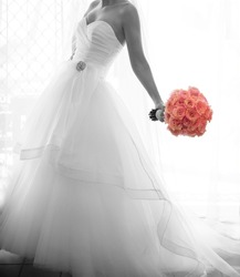 Softly focused monotone bridal image in window light with colorized rose bouquet