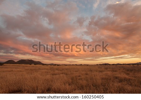 Softly orange cloudy Autumn sunset over dry grassland and hills/Uplifting Orange and Blue Clouds Spread Outwards in Autumn Dusk Cloudscape Scenic/Colorful Fall clouds in rural cloudscape