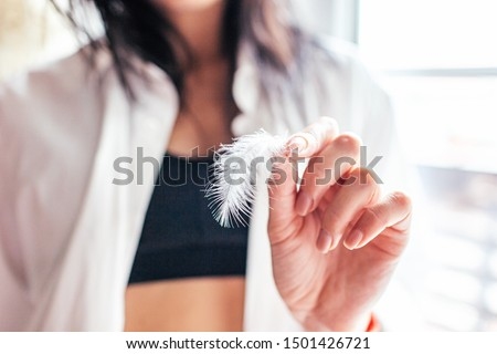 Softness Concept. Closeup Of Beautiful Woman's Hands With Healthy Soft Skin Holding Light White Feather. Health And Body Care Concepts