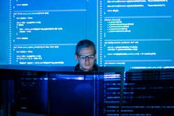 Software developer freelancer man male work with program code C++, Java, Javascript on wide displays at night. Develops new web desktop mobile application or framework. Projector futuristic background