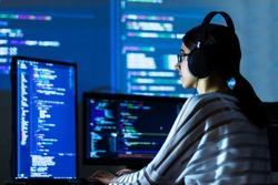 Software developer freelancer woman female in glasses work with program code C++ Java Javascript on wide displays at night Develops new web desktop mobile application or framework Projector background