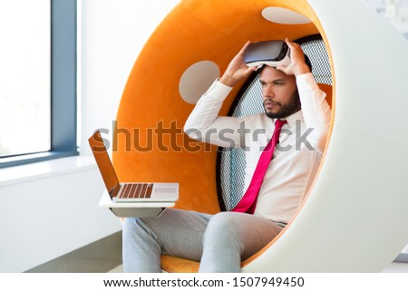 Software developer testing interactive product. Man in office clothes sitting in interactive chair with laptop and taking off virtual reality goggles. Simulation concept