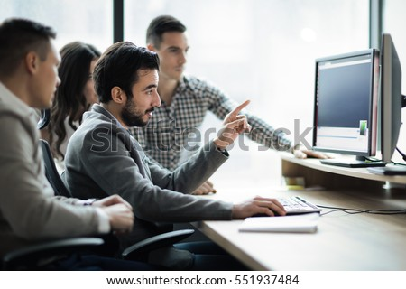 Software engineers developing applications together in office