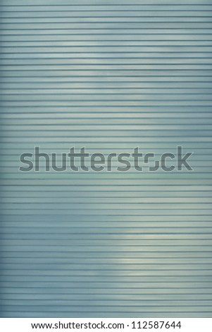 Softy frosted opaque glass with with diffuse lines and shadows playing across the surface. Greenish blue colors - stock photo