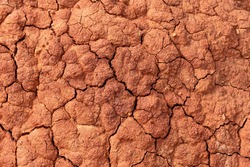 Soil erosion. Cracks in red clay ground. Arid climate. Dry dewatered sandy earth. Abstract texture or background. Horizontal format.