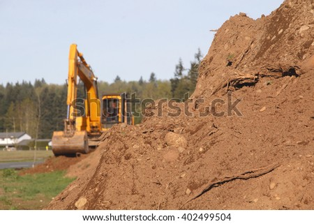 Soil or dirt in the foreground with an industrial shovel in the background/Heavy Lifters and Moving Earth/An industrial shovel a pile of dirt.