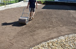 soil preparation before sowing the lawn with a soil cultivator. soil loosening, raking, sowing. the seed is repaired by rolling with a metal hand roller, which is filled with water, it will be heavier