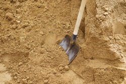 Soil with shovel, teel shovel be used for scoop sand to construct the building background, front view, Sharp shovel on cultivated farm field, Digging soil, Shovel putted into heap of ground