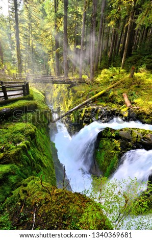 Sol Duc Falls with sunbeams through mist over wooden foot bridge, Olympic National Park, Washington, USA