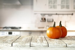 Solar autumn pumpkin in the kitchen on a white table