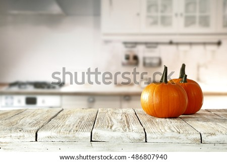Solar autumn pumpkin in the kitchen on a white table