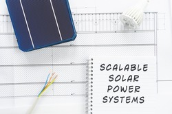 Solar cells, wires and led bulb note pad with Scalable Solar Power Systems written on it in a conceptual image to scale solar power production