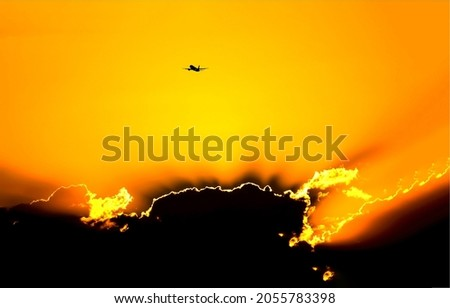 Solar eclipse in sunset sky. A plane in the sky at sunset. Sunset sky plane silhouette
