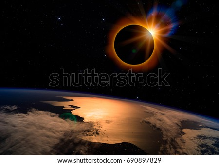 Shutterstock Solar eclipse with orange halo over the planet Earth, on dark starry sky