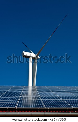 Solar energy panels on a roof and a wind energy tower in the background