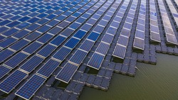 Solar farm panels in aerial view, rows array of polycrystalline silicon solar cells or photovoltaics in solar power plant floating on the water in lake, Alternative renewable energy.