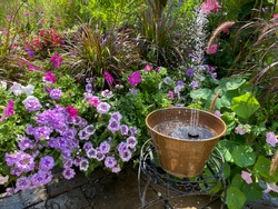 Solar fountain in a copper garden pot spraying the containers of bountiful petunias.