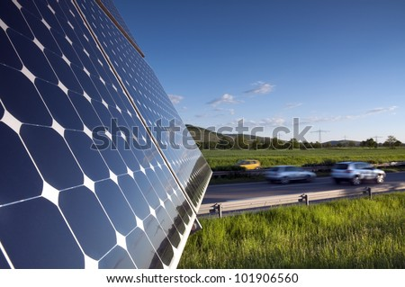 Solar Panel Against Blue Sky With Green Landscape And Highway