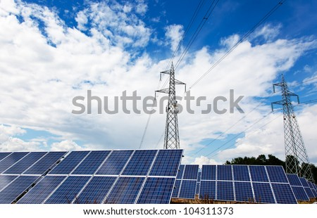 Solar panel and power lines over a blue cloudy sky.