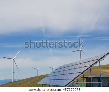 Solar panel and row of wind turbines under cloud blue sky at Ellensburg, Washington, US. Power plant generates renewable energy from sun and wind. Clean, sustainable power concept. Green energy source
