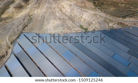 Solar panel farm, alternative green eco-friendly energy. Panels rows along the dry lands. Huge Photovoltaic from an aerial drone point. Top view.
