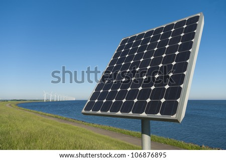 solar panel in front of a row wind turbines on a dutch dike - stock photo
