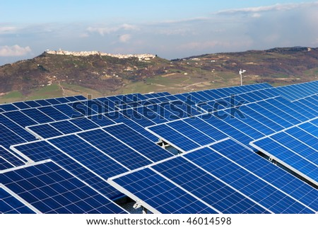 Solar panel installation with village in background in Molise (selective focus on panels)