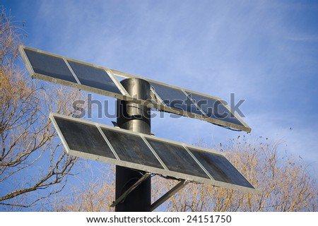 Solar panel on a pole with sky and tree background in winter time - stock photo