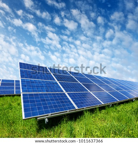 Solar panel on blue sky background. Green grass and cloudy sky. Alternative energy concept #1011637366