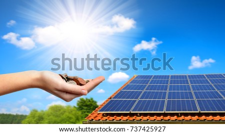 Solar panel on the roof of the house and coins in hand. The concept of money saving and clean energy. #737425927
