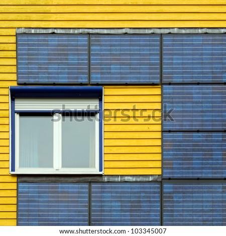 solar panel on yellow facade - stock photo