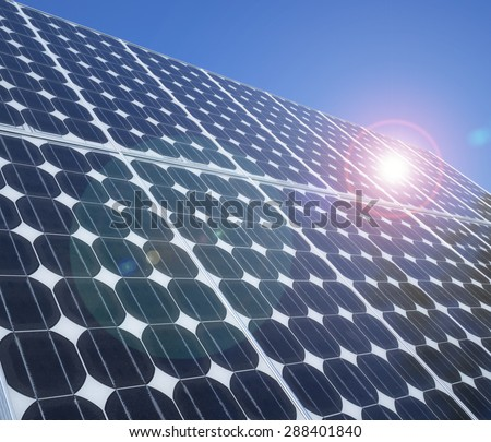 Solar panel photovoltaic cells array close up with blue sky, lens flare and copy space. Solar energy is an eco-friendly power source which uses the sun to generate clean renewable energy.