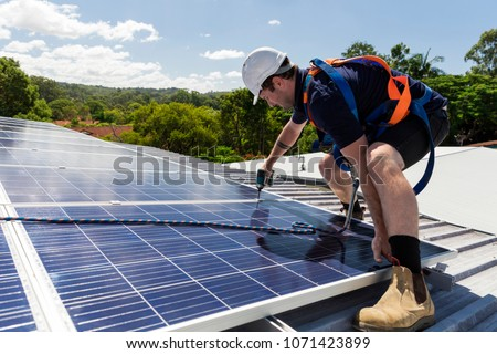 Solar panel technician with drill installing solar panels on roof on a sunny day #1071423899