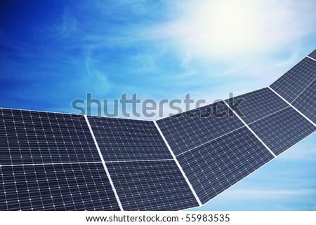 Solar panels against nice cloudy sky with sun