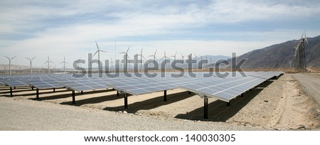 Solar Panels AKA- Photovoltaic Cells in a SOLAR FARM with Wind Turbines in the background collect and produce Electricity from Natural Renewable Resources of the Sun and Wind producing GREEN ENERGY